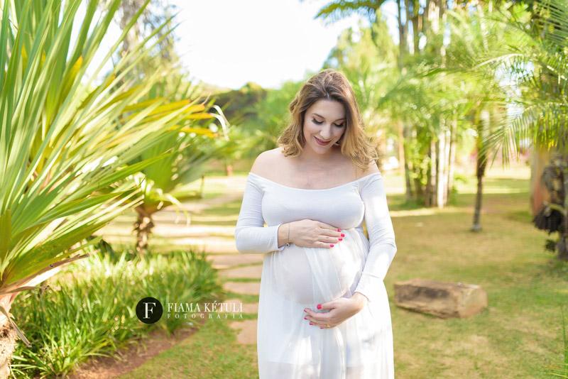 Grávida em ensaio fotográfico ao ar livre com vestido branco