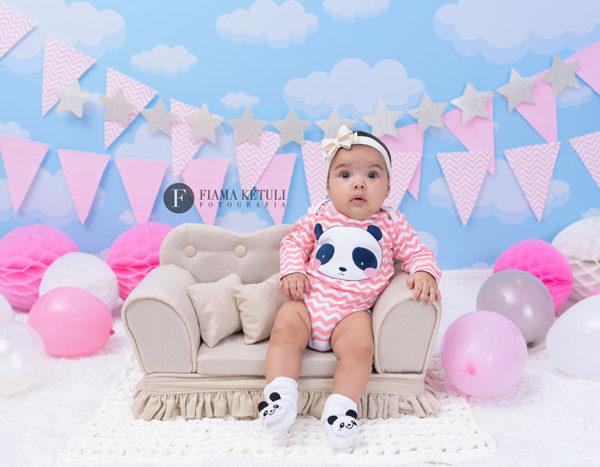 Bebê fazendo ensaio de acompanhamento em estúdio com o cenário da fotógrafa
