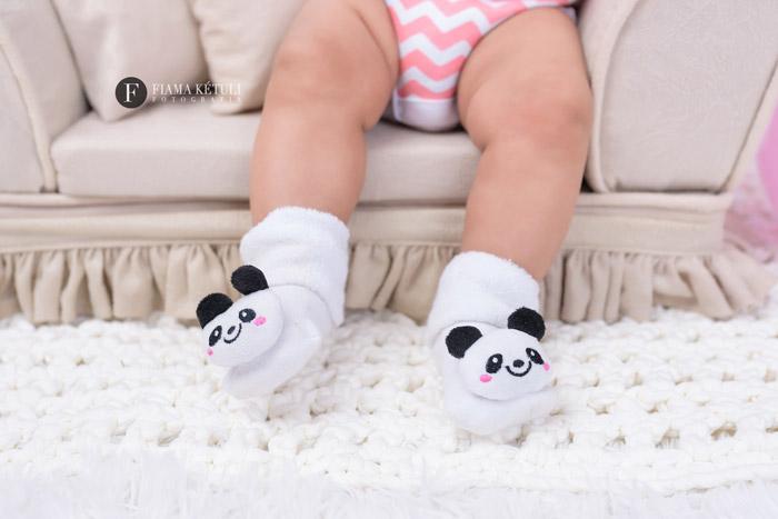 Foto do pézinho do bebê com meia de panda em estúdio fotográfico
