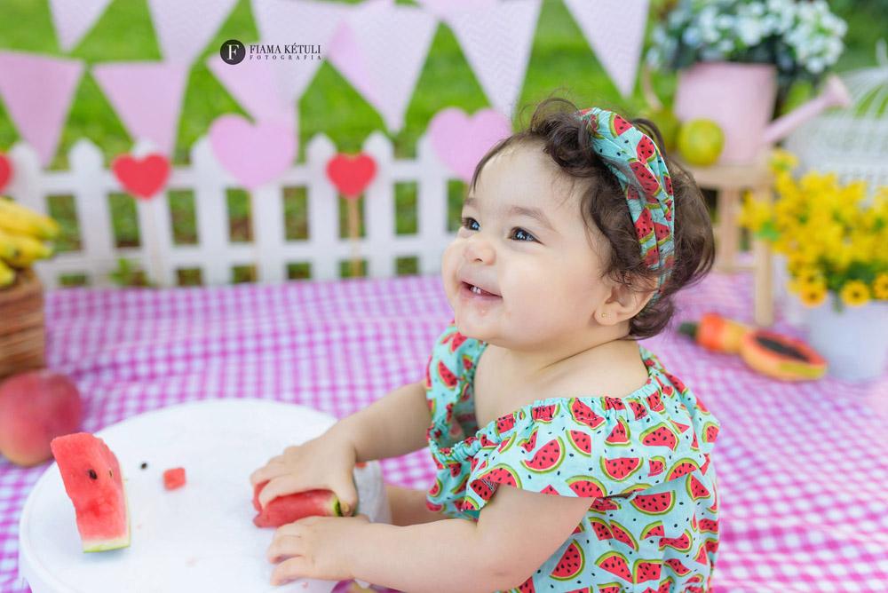 Ensaio de bebê no cenário comendo frutas